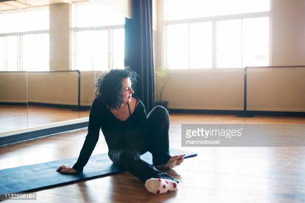 "mature woman instructor of stretching class. - ""martine doucet"" or martinedoucet stock pictures, royalty-free photos & images"