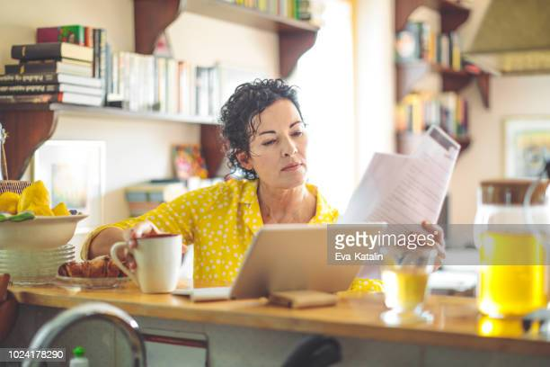 Mature woman is checking her finances at home