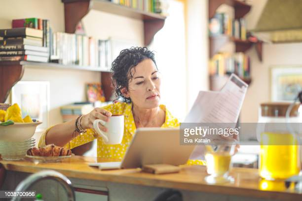 mature woman is checking her finances at home - budget stock pictures, royalty-free photos & images