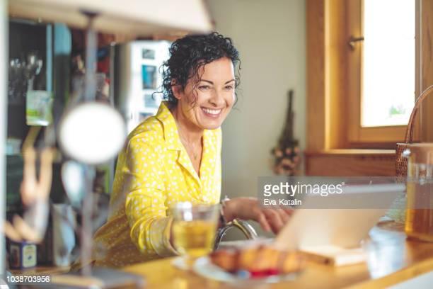 rijpe vrouw is het controleren van haar financiën thuis - alleen één oudere vrouw stockfoto's en -beelden