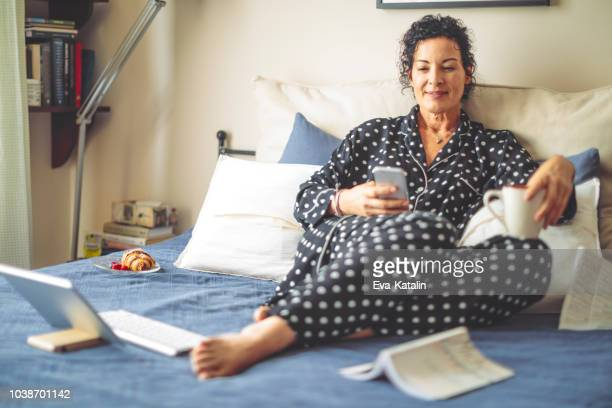 Mature woman is getting up and reading news online