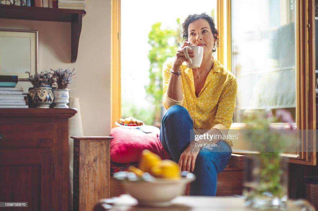 Mulher madura é ter o café da manhã em casa : Foto de stock