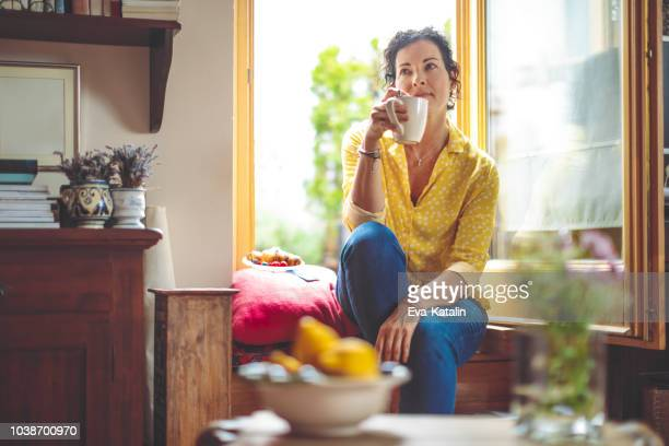 mature woman is having the morning coffee at home - lazer imagens e fotografias de stock