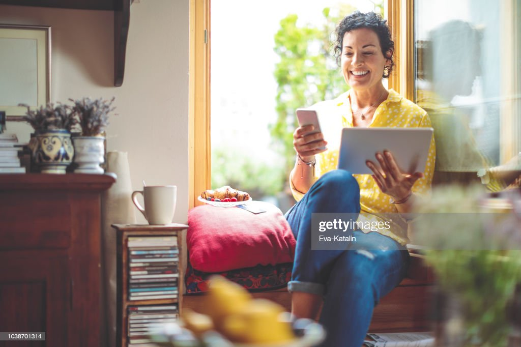 Mature woman is purchasing online at home : Stock Photo