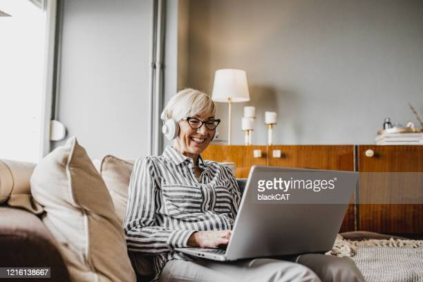 mature woman is working from home - surfing the net stock pictures, royalty-free photos & images