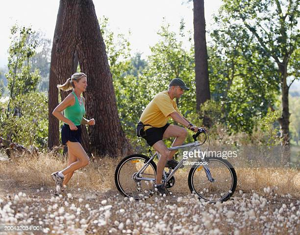Mature woman jogging on dirt track behind mature man riding bicycle