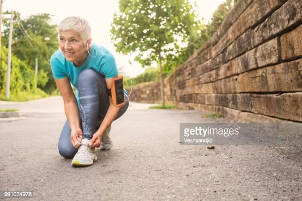 ältere frau joggen - frau gefesselt stock-fotos und bilder