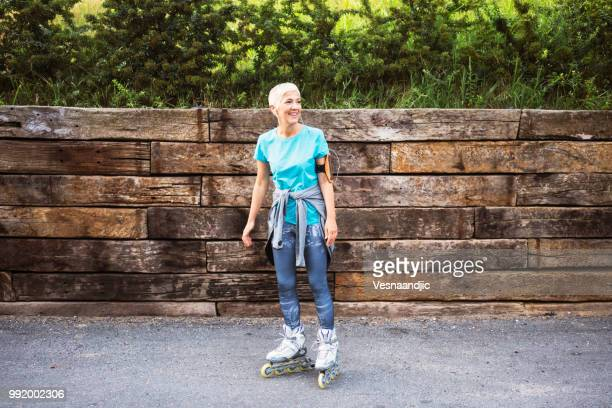 mature woman jogging - inline skating stock pictures, royalty-free photos & images
