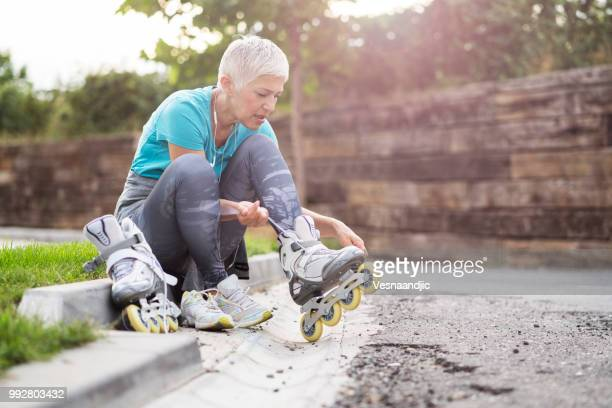 mature woman jogging - inline skate stock photos and pictures