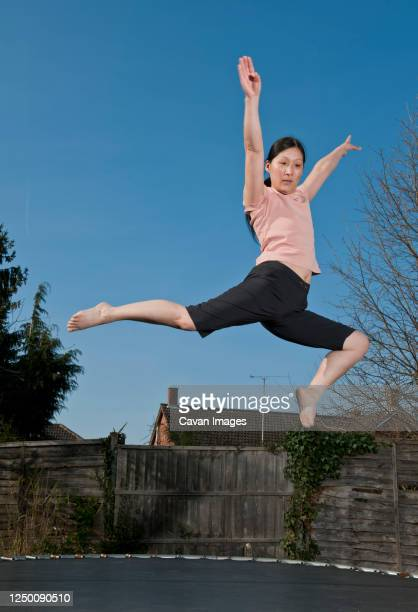 mature woman jumping on trampoline in woking - england - individual event stock pictures, royalty-free photos & images