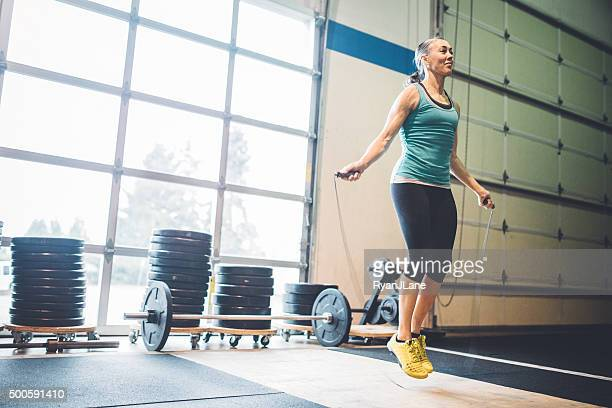 Mature Woman Jumping Rope in Gym Setting