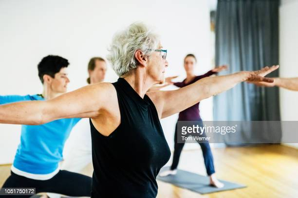 mature woman keeping fit in yoga class - fitness or vitality or sport and women stock photos and pictures