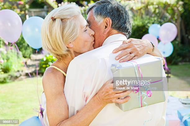 mature woman kisses mature man. - anniversary stock pictures, royalty-free photos & images