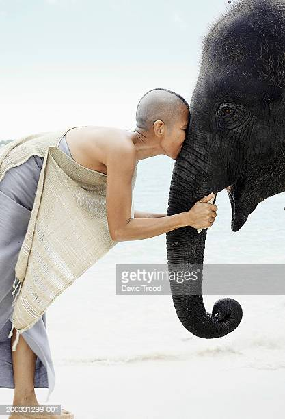 Mature woman kissing young indian elephant, side view