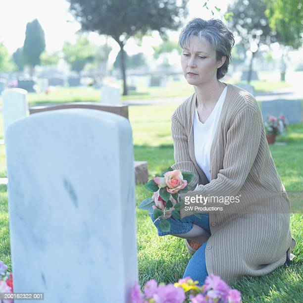 Mature woman kneeling beside tombstone, holding flowers
