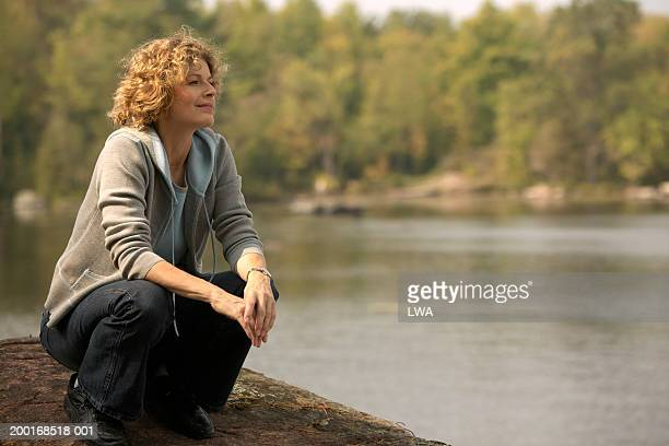 mature woman kneeling down near lake - lakeshore stock pictures, royalty-free photos & images