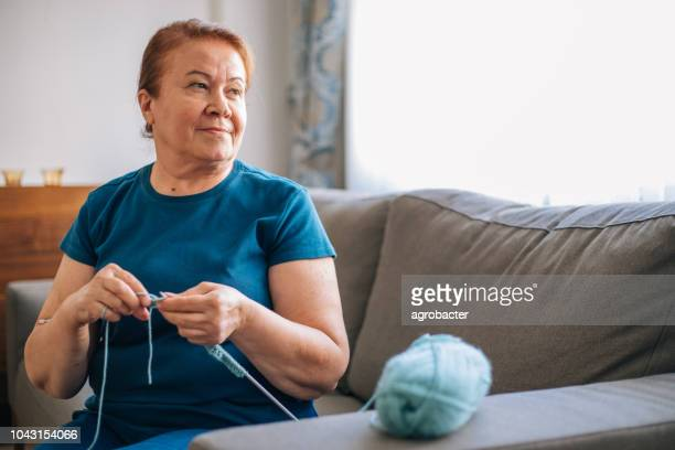 mature woman knitting at home - fat old lady stock photos and pictures