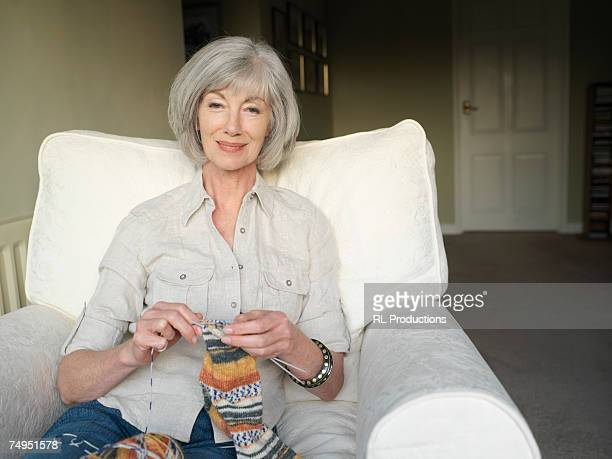 Mature woman knitting in armchair, portrait
