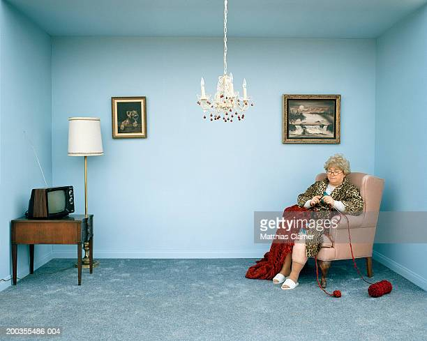 Mature woman knitting in living room