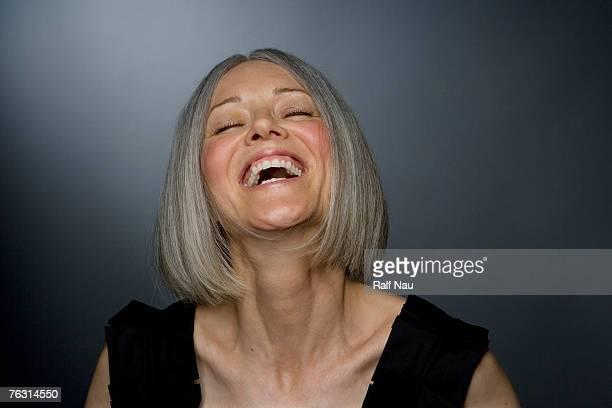 mature woman laughing, eyes closed, close-up - 頭をそらす ストックフォトと画像