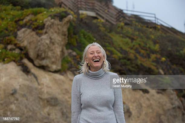 mature woman laughing on beach - high collar stock pictures, royalty-free photos & images
