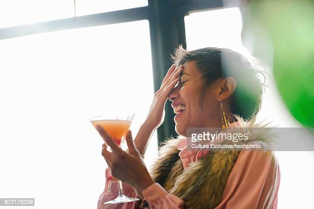 mature woman laughing whilst drinking cocktail in recreational bar - heshphoto foto e immagini stock