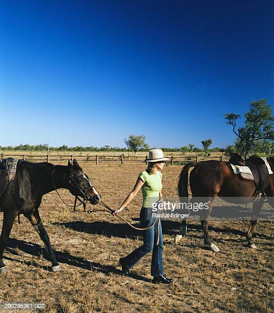 Mature woman leading horse across dry paddock, side view
