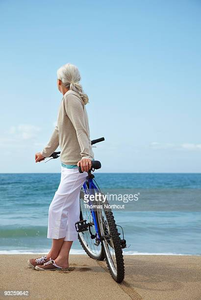 mature woman leaning against bicycle at beach. - legs crossed at ankle stock pictures, royalty-free photos & images