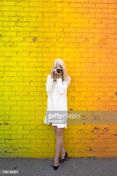 mature woman leaning against coloured wall taking picture with camera - long bright yellow dress stock pictures, royalty-free photos & images