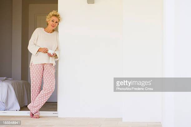 Mature woman leaning against wall in pajamas with cup of coffee