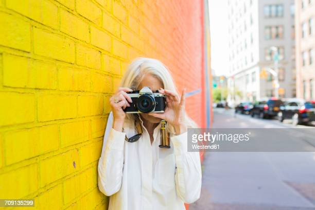 mature woman leaning against wall taking picture with camera - white hair stock photos and pictures