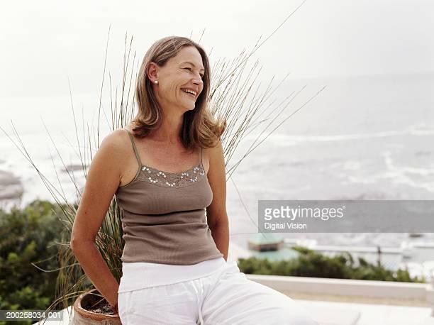 mature femme s'appuyant sur le balcon au bord de l'océan, souriant - femme 50 ans brune photos et images de collection