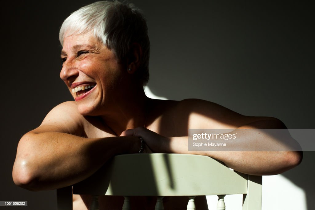 A mature woman leaning on the back of a chair in the sunlight : Stock-Foto