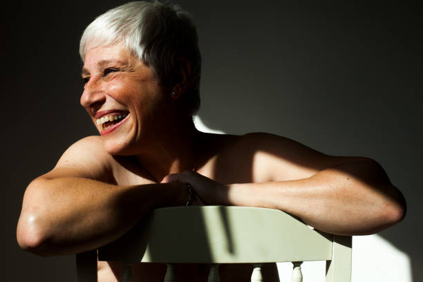A mature woman leaning on the back of a chair in the sunlight