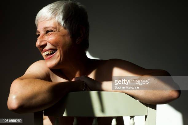 a mature woman leaning on the back of a chair in the sunlight - parte del cuerpo humano fotos fotografías e imágenes de stock