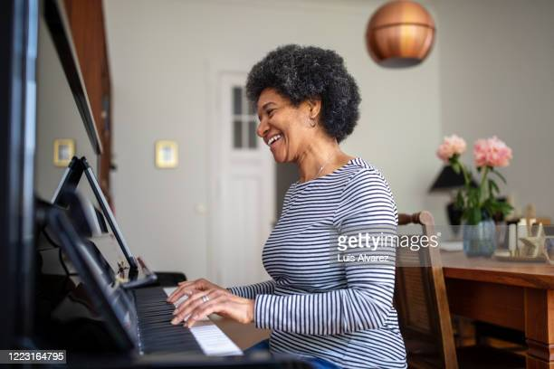 mature woman learning playing piano during home quarantine - disruptaging stock-fotos und bilder