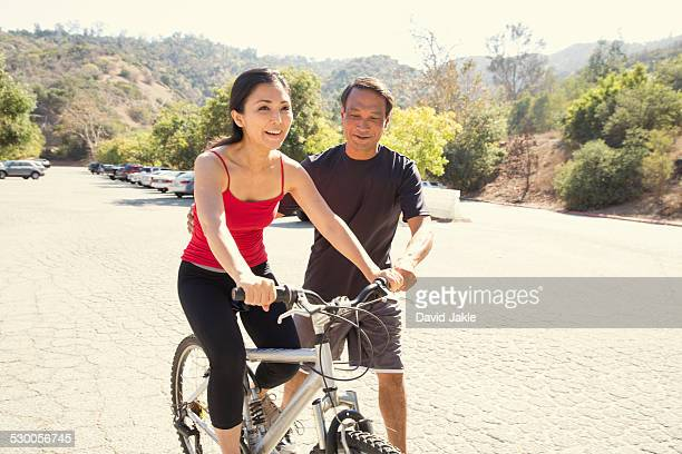 Mature woman learning to ride bicycle in park