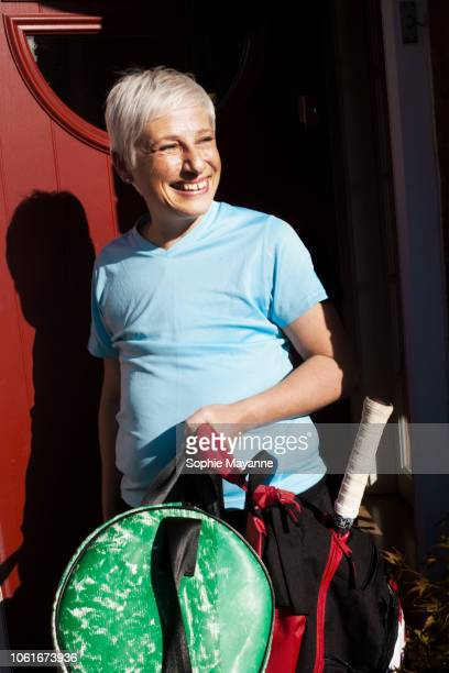 A mature woman leaving a house in sports wear