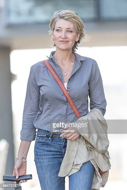 Mature woman leaving hotel with wheeled suitcase