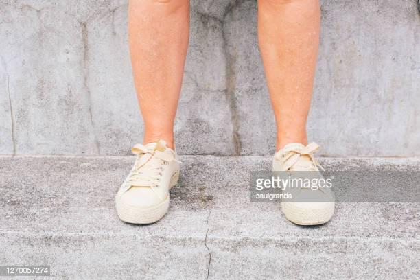 mature woman legs against cement - chaussures beiges photos et images de collection