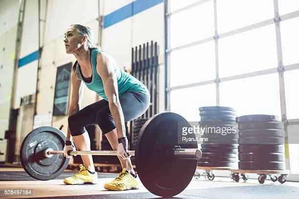 mature woman lifting weights in gym setting - weight training stock pictures, royalty-free photos & images