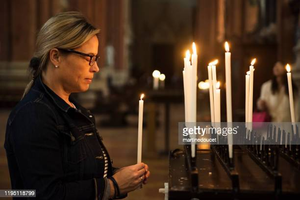 volwassen vrouw verlichting kaarsen in de kerk. - gelovige stockfoto's en -beelden