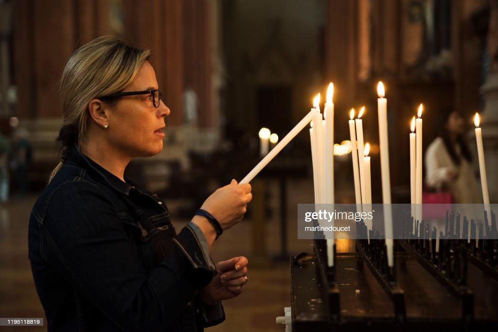 Mature woman lighting candles in church. : Stock Photo