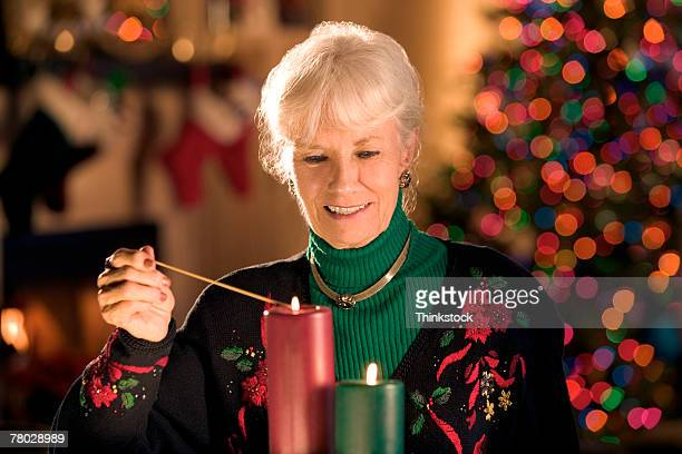A mature woman lights decorative candles at Christmastime.