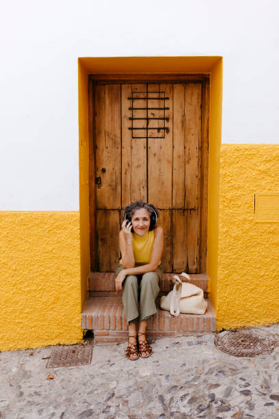 Mature woman listening music through headphone while sitting against old door