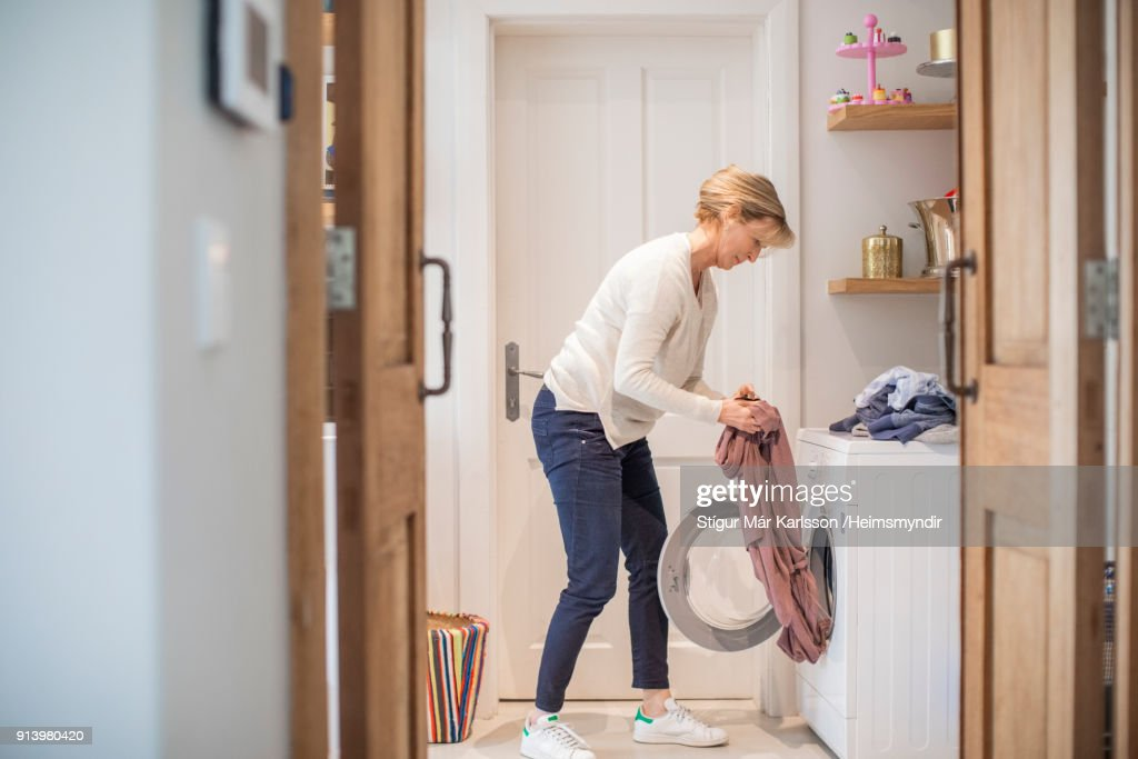 Mature woman loading clothes in washing machine : Stock Photo
