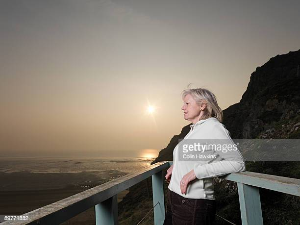 mature woman looking across sea - colin hawkins stock pictures, royalty-free photos & images