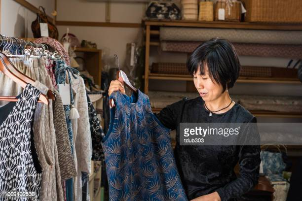 mature woman looking at a dress in a textile shop - vanguardians stock pictures, royalty-free photos & images
