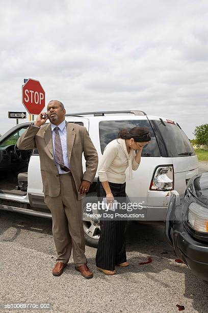 Mature woman looking at accident damage to car, man using mobile phone