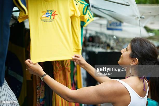 Mature woman looking at brazilian football shirt on market stall, Ipanema, Rio De Janeiro, Brazil